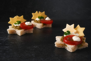 Spoed Foto op Canvas Buffet, Bar vegetarian canapes for christmas with tomato, pesto and cheese in star shape on a dark stone slab with copy space