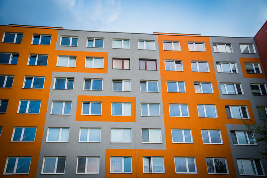 Facade of high modern apartment building under blue sky. Real estate background
