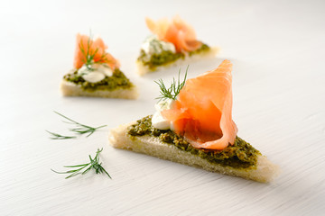canapes with smoked salmon, pesto, cream and dill garnish on a light background with copy space