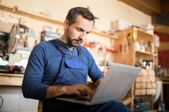 Portrait of mature worker using laptop in carpenters workshop interior, copy space