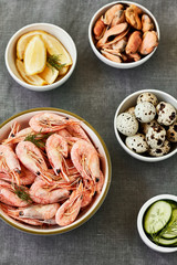 Healthy seafood ingredients -shrimp, mussels, quail eggs, lemon and cucumber on a gray background, top view. Salad ingredients