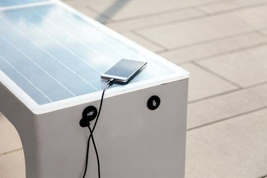 Solar panel on city bench outdoors. Mobile phone charging via USB from solar power. Alternative electricity source. Concept of sustainable resources, free, renewable energy, ecology, modern technology