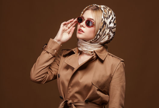 Portrait of young beautiful woman in trendy trench coat over beige background. Elegant fashion look.