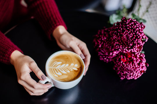 Cup of cappuccino in hand