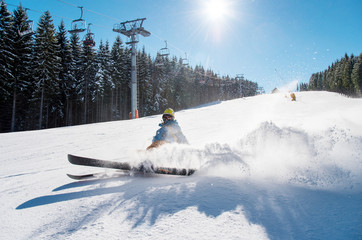 Skier falling on the slope on fresh powder snow at winter resort. Blue sky, sun and winter forest on the background copyspace adventure extreme adrenaline active lifestyle concept