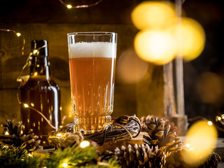 Fotorolgordijn Bier / Cider Beer in glass on wooden background with Christmas lights and pine cones