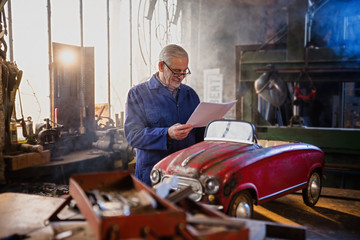A senior man in his workshop restoring an old pedal car
