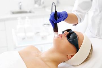 Fototapeta  Zabieg laserowy na twarz. Kobieta w salonie kosmetycznym podczas zabiegu z użyciem lasera. obraz
