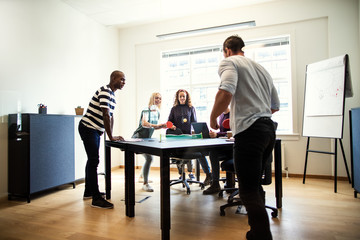 Smiling colleagues playing table tennis together in an office