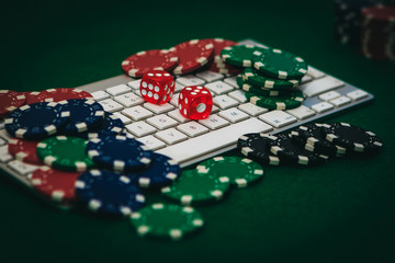 Side view of a green poker table with some poker cards on a keyboard. Betting on-line concept