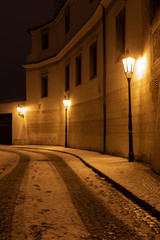 Narrow snow covered street in historic city of Prague. Empty street and car tracks on cobblestoned street in night.