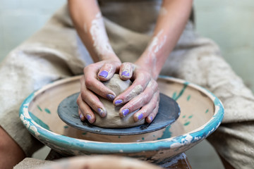 Workmanship concept. Cropped photo of concentrated calm lady artist in her workwear she sit inside workspace make product from clay hold piece of clay focus on hands