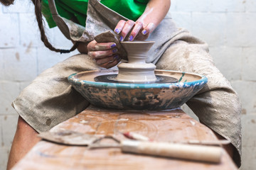 Master class concept. Low angle top view photo of workmanship lady artist in her workwear she sit inside workspace using circular wheel and special tool to made clay cup shape