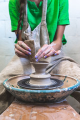 Master class concept. Vertical photo of concentrated lady artist in her casual green t-shirt workwear she sit indoor workspace using circular wheel to make handmade tableware production