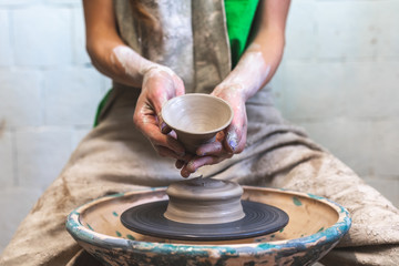 Master class concept. Cropped close up photo of artist lady in her workwear she sit indoor workspace show raw ceramics tableware product ob camera