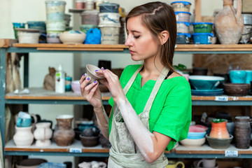 Master class concept. Half turn workmanship calm lady in her casual green t-shirt workwear she stand inside workspace check quality of ceramics cup hold mug in hands