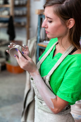 Master class concept. Vertical profile side view photo of confident lady in her casual green t-shirt workwear she stand indoor workspace look on small cup in hands check quality of product