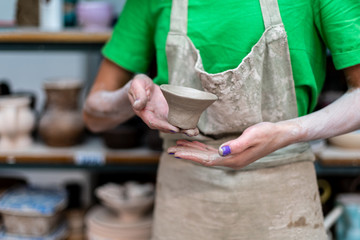 Master class concept. Cropped close up photo of artisan artist lady in her workwear she stand inside workspace show handmade ceramics cup on camera