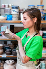 Master class concept. Profile side view photo of workmanship attractive peaceful calm lady in her casual green t-shirt workwear she stand inside workspace correct form clay cup by sponge