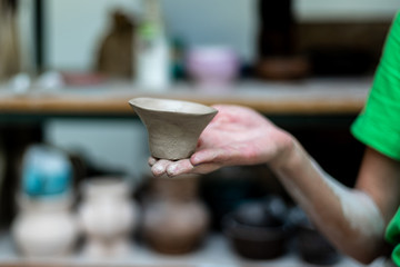 Master class concept. Cropped close up photo of workmanship lady in her workwear she stand indoor workspace hold small ceramics clay tea cup on hand