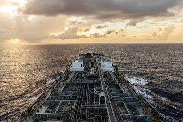 Oil product tanker is underway at sea at sunset.