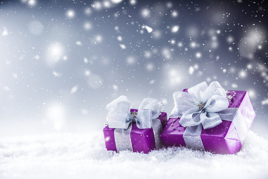 Christmas luxury purple gifts in snow and abstract snowy atmosphere