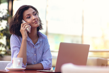 Businesswoman Using Phone While Working In Coffee Shop