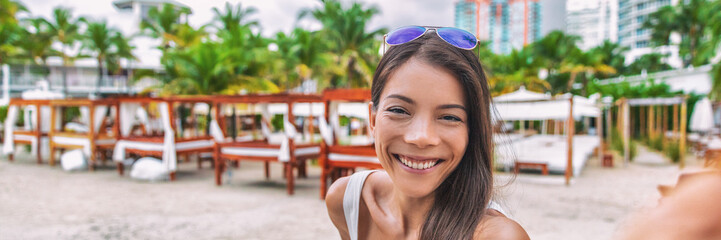 Wall Mural - Selfie travel vacation Asian tourist on luxury resort hotel travel summer destination holiday. Vacations banner panorama girl smiling.