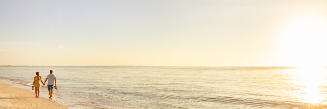 Beach couple walking on beach watching sunset tropical landscape banner panoramic background. Summer holidays destination panorama. relaxing vacation - travel tourists.