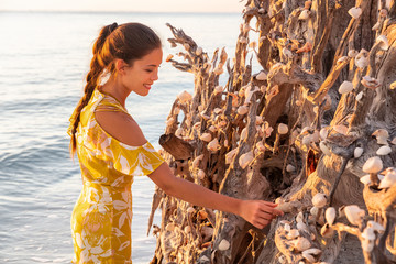 Beach seashells woman putting seashell conch shell on tree trunk at Lovers Key Shells in Florida near Fort Myers, USA.