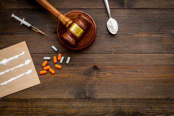 Drugs addiction, arrest for drugs. Pills, spoon with powder, syringe on dark wooden background top view copy space