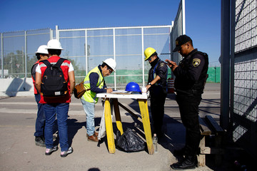 Workers sign a list before entering the construction site of the new Mexico City International Airport in Texcoco