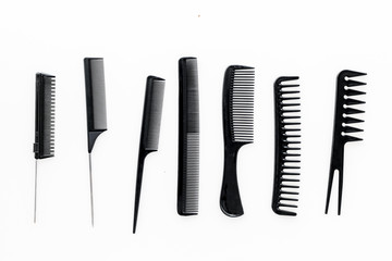 female hairdresser desk with accessories and combs on white background top view