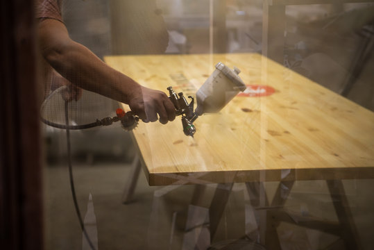 Master painter in a factory - industrial painting wood with spray gun. Soft focus