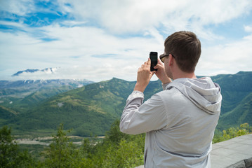 A man takes a photo of a mountain