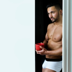 Man in white panties drinks coffee. Tea for a bearded man, a successful morning. Handsome sexy guy. Plans for the day, dreamy look. Privectalny handsome man with bare chest