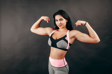Strong fitness girl shows biceps in the studio