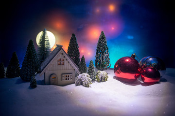 Christmas and New Year miniature house in the snow at night with fir tree. Little toy house on snow with tree. Festive background. Christmas decorations.