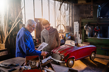 A grandfather and his grandson restoring an old pedal car