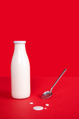 Botella de leche con cuchara metálica y gotas de leche. Fondo rojo