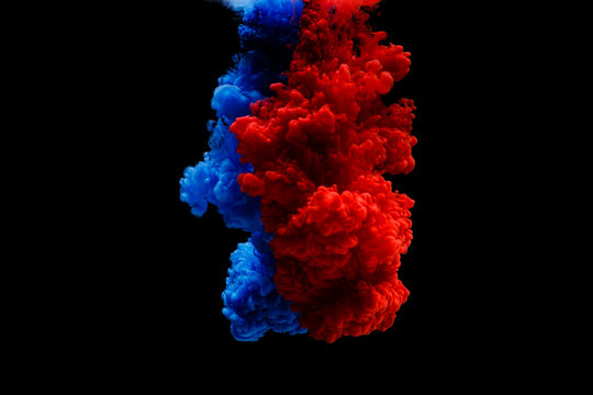 Mix of colored ink in water creating abstract shape, isolated on black background. Two paints blue red mixing together in water