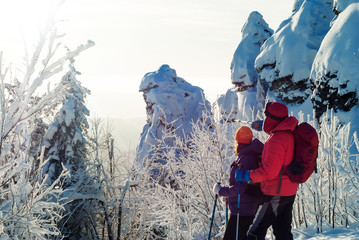 man and woman travelers in winter mountains look into the distance standing nearby against the snowy rocks on a sunny frosty day