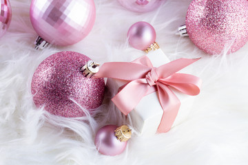 Pink Christmas decorations with gift box on white fur background close up