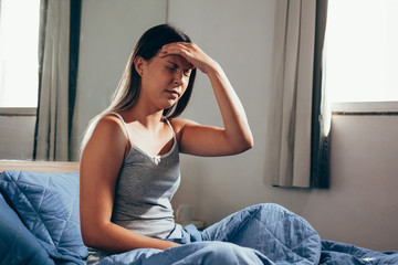 Young woman with headache sitting on her bed