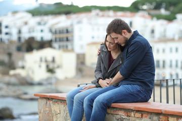 Sad woman and man comforting her on a ledge