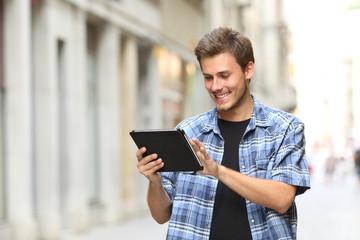 Happy man walking browsing tablet online content