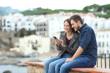 Happy couple on a ledge checking smart phone