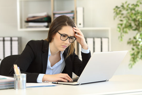 Worried office worker reading bad online news
