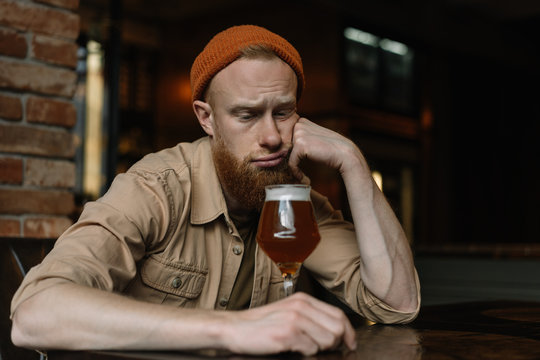 Bearded hipster man with emotional depressed face sitting alone and drinking alcohol beer in pub, he unhappy, tired and need support. Health disorder. Alcohol abuse Treating alcoholism concept