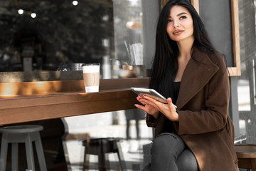 Beautiful girl uses a tablet and drinks coffee, sitting in a cozy cafe.